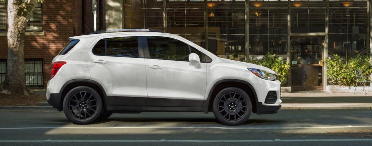 A white 2022 Chevy Trax is shown from the side parked on a city street.