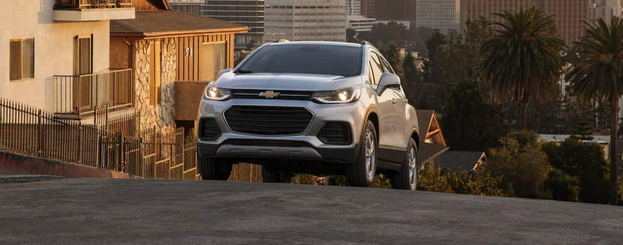 A silver 2022 Chevy Trax is shown driving in a city.