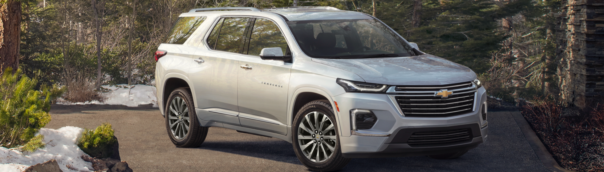 2022 Chevy Traverse Premier next to a cabin in the woods.