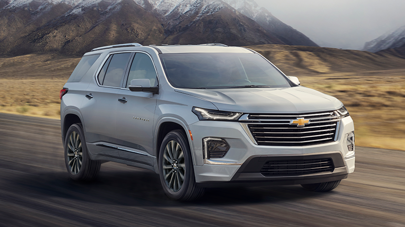 2022 Chevy Traverse Premier driving on the road in front of some mountains