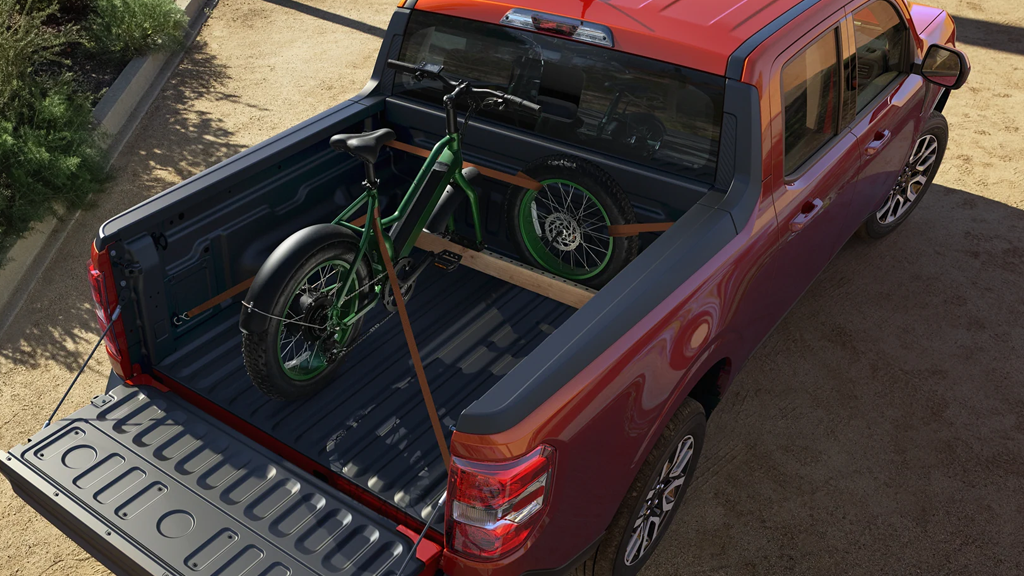 2022 Ford Maverick Lariat in the color Hot Pepper Red with a bike in the truck bed