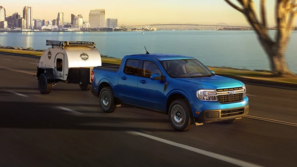2022 Ford Maverick Lariat in the color Velocity Blue hauling a trailer away from the city