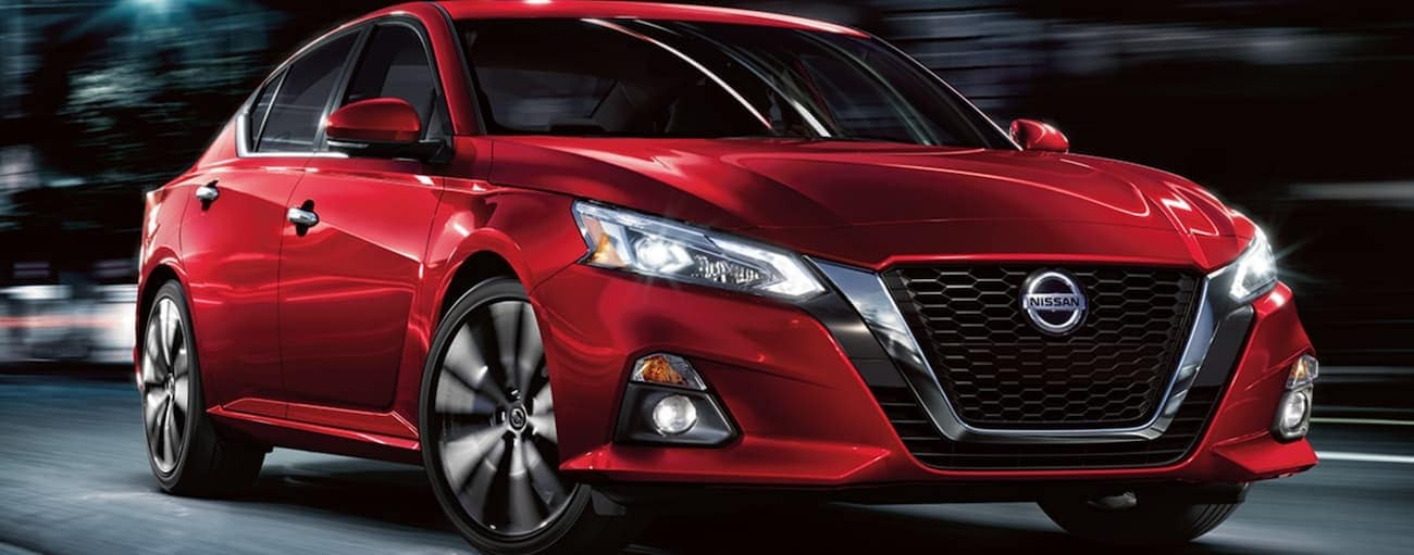 A red 2021 Nissan Altima is driving on a city street at night.