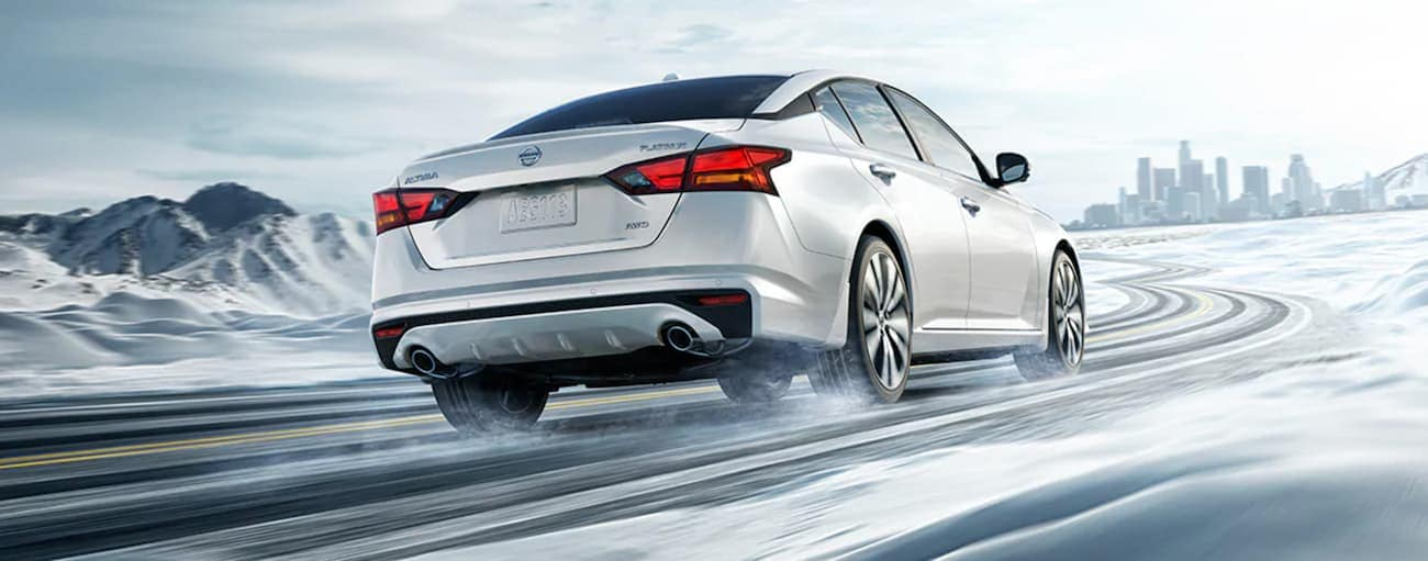 A white 2021 Nissan Altima is driving on a snowy road toward a city.