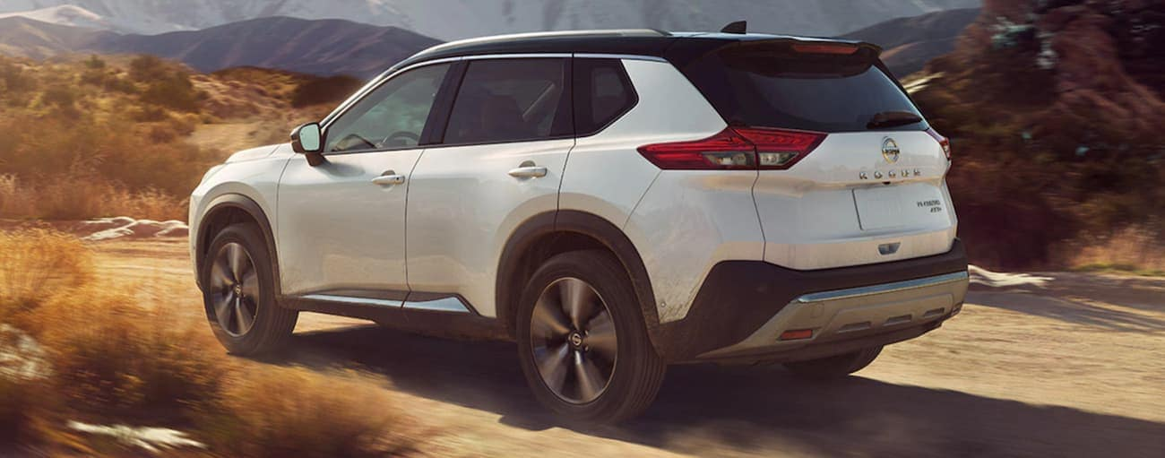 A white 2021 Nissan Rogue is driving on a dirt road.