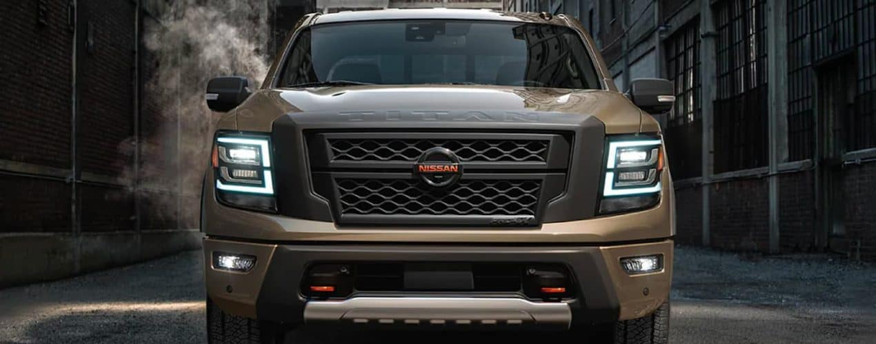 A brown 2021 Nissan Titan is shown from the front parked in an alleyway.
