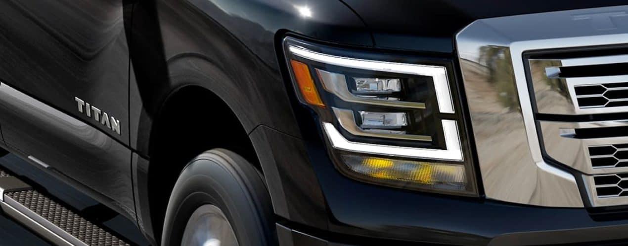 A close up shows the LED headlight on a black 2021 Nissan Titan.