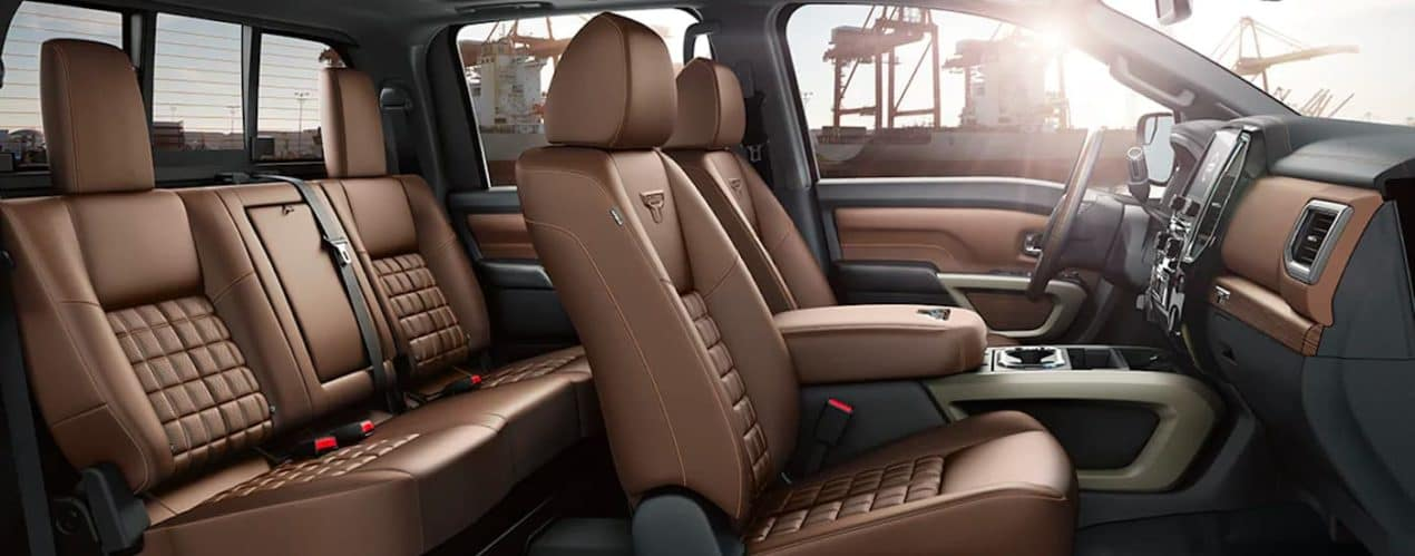 The brown interior and seating is shown from the passenger side of a 2021 Nissan Titan.