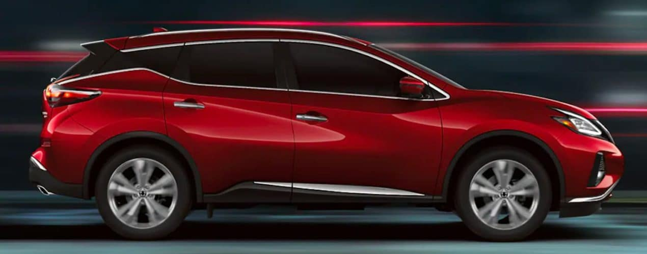 A red 2021 Nissan Murano is shown from the side speeding through the city.