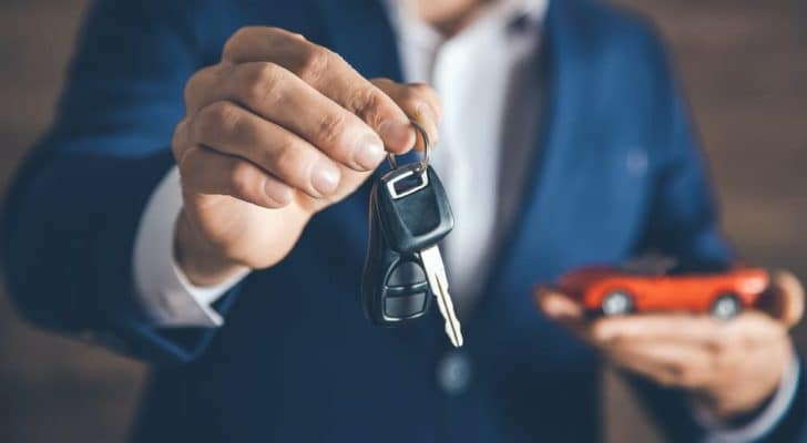A man in a blue suit is holding out a set of car keys with one hand and has a toy car in the other hand.