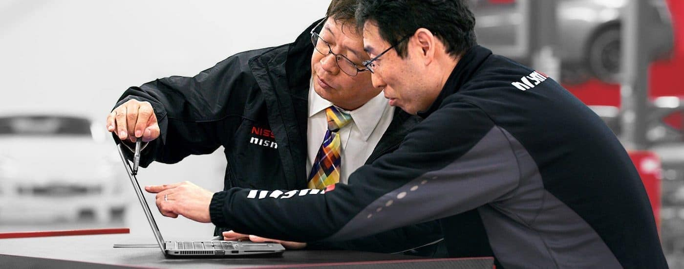A close up shows two Nismo engineers working on a laptop.