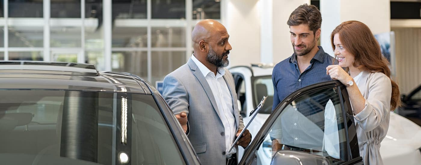 A salesperson is showing a couple a vehicle at an Indiana Nissan dealer.
