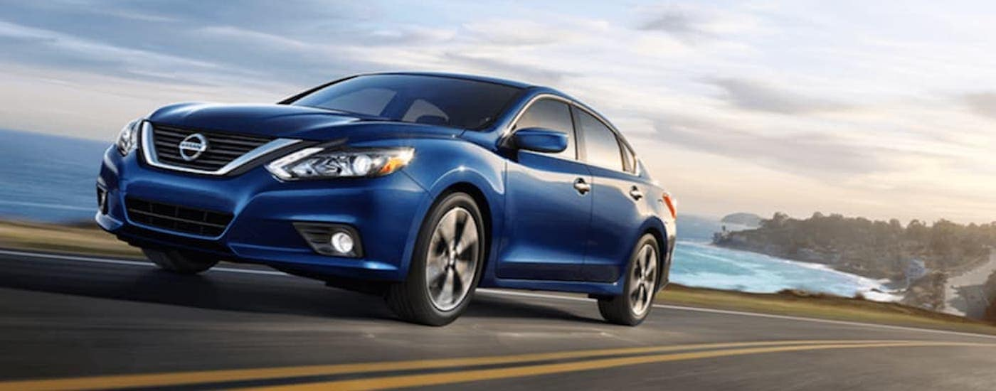 A blue 2018 Nissan Altima from a used Nissan dealership is driving past the ocean.
