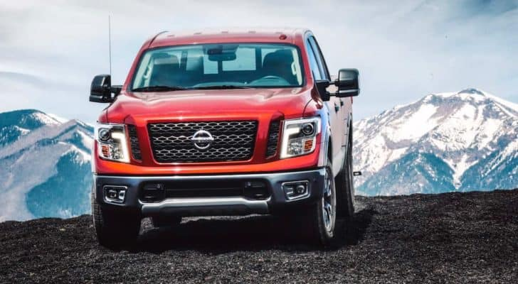 A red 2018 Nissan Titan is parked in front of snow covered mountains.