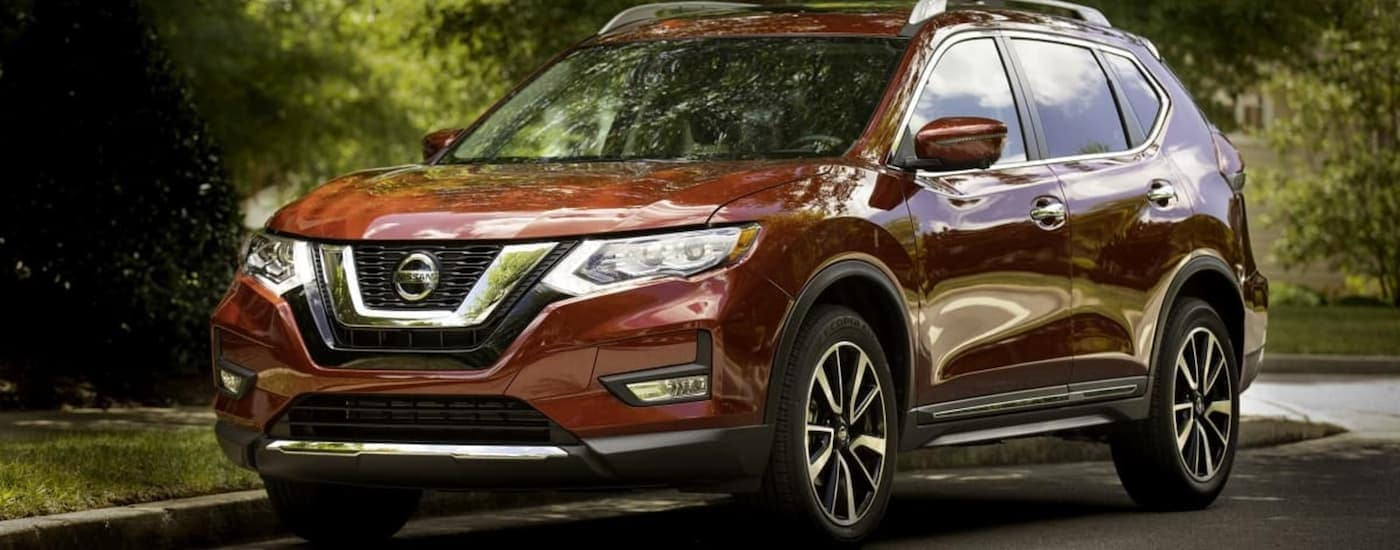A red 2019 Nissan Rogue is on a tree-lined street.