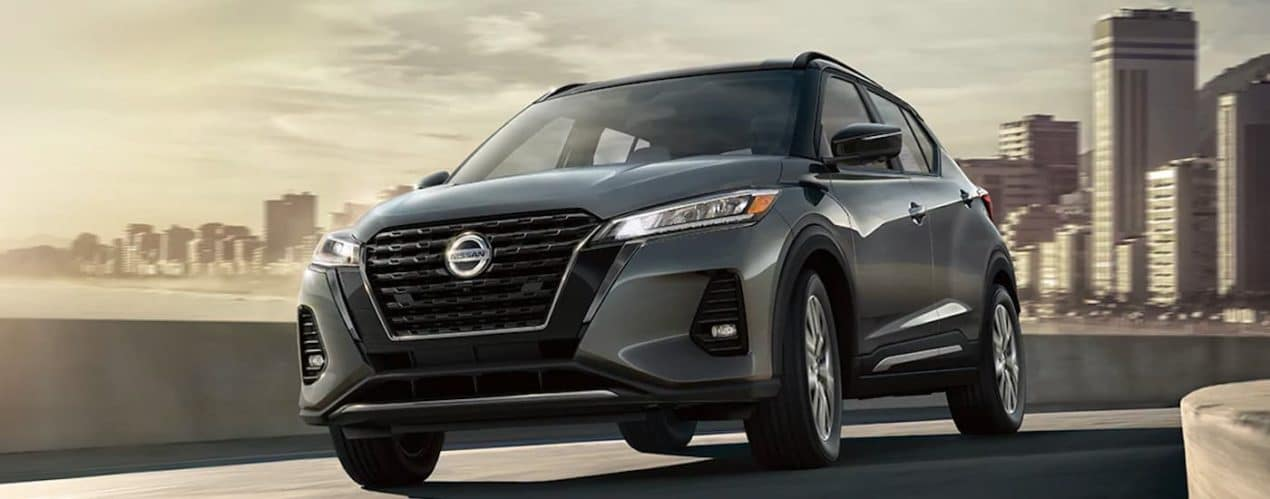 A dark gray 2021 Nissan Kicks is shown driving down the highway away from a city.