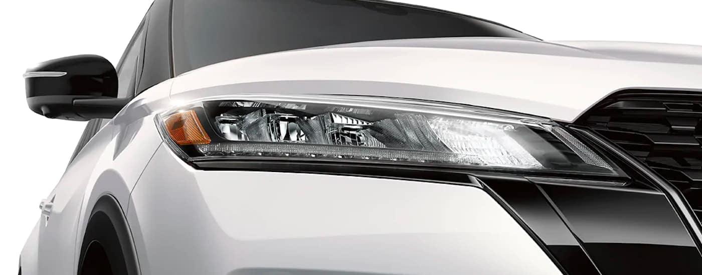 A close up shows the LED headlight on a white2021 Nissan Kicks.