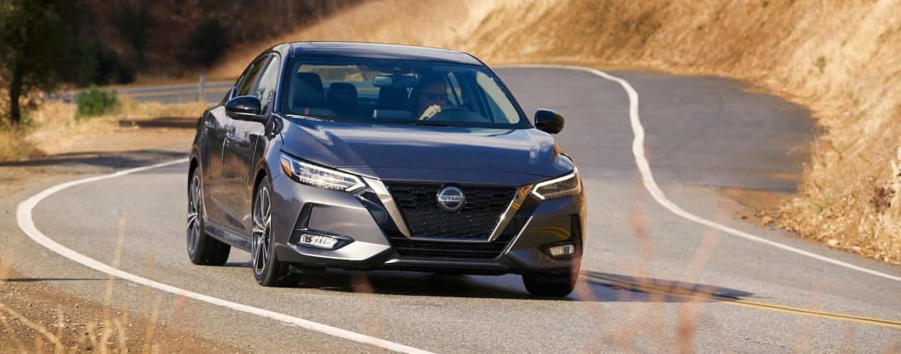 A gray 2021 Nissan Sentra is shown from the front driving on a winding road.