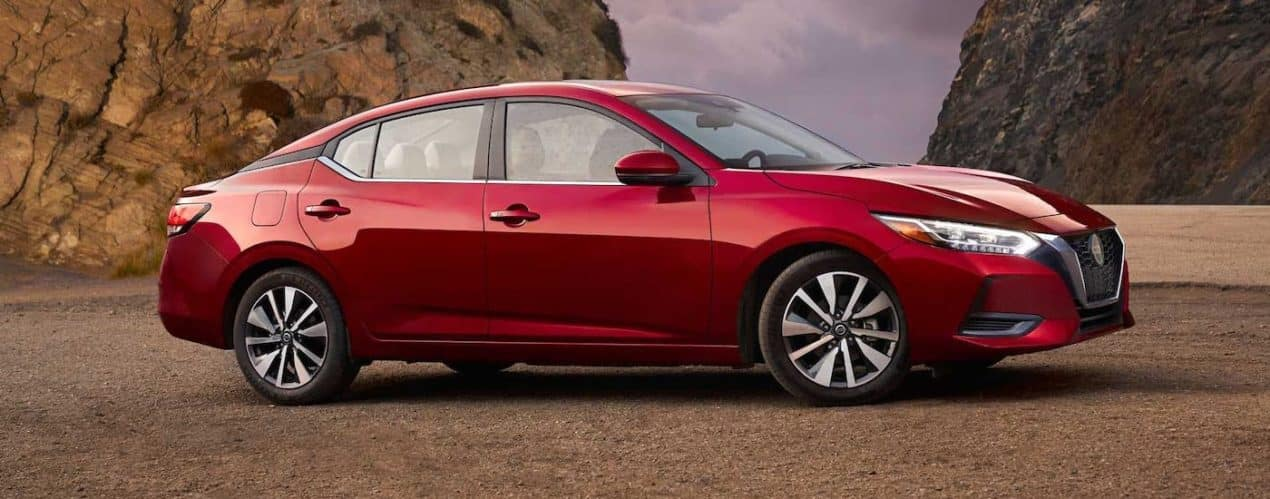 A red 2021 Nissan Sentra is shown from the side while parked in front of rocks.