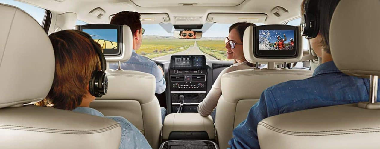 A family is shown in a 2021 Nissan Armada from the rear seats while the kids watch the infotainment screens.