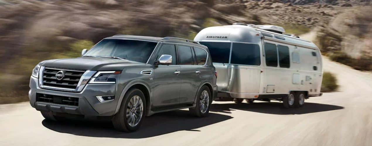 A grey 2021 Nissan Armada is towing an Airstream past rocks.