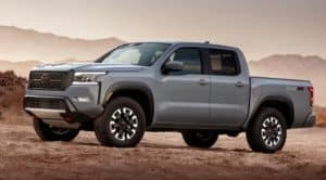 A grey 2022 Nissan Frontier is shown facing left at sunset.