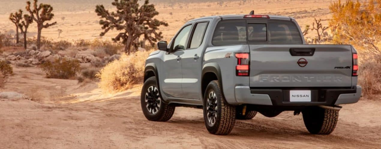 A grey 2022 Nissan Frontier is shown from the rear in a desert.