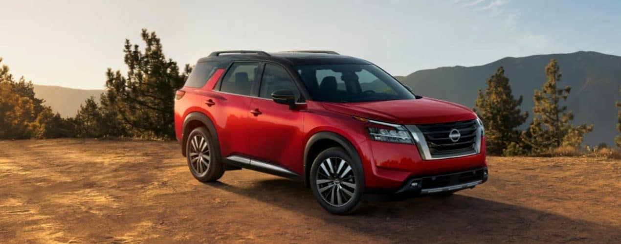 A red 2022 Nissan Pathfinder is parked off-road with a mountain view.