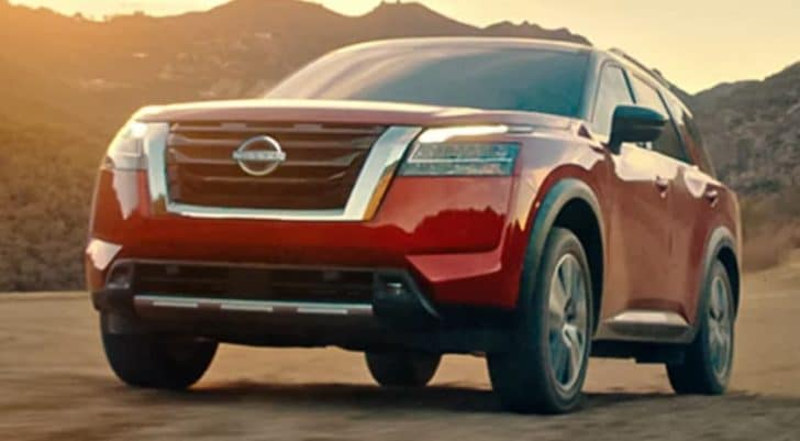 A red 2022 Nissan Pathfinder is driving on dirt in front of mountains.