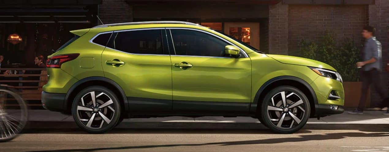 A green 2021 Nissan Rogue Sport is parked on a city street.