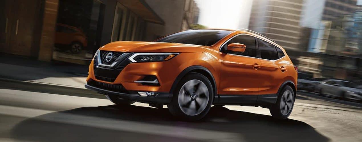 An orange 2021 Nissan Rogue Sport is taking a corner on a city street.