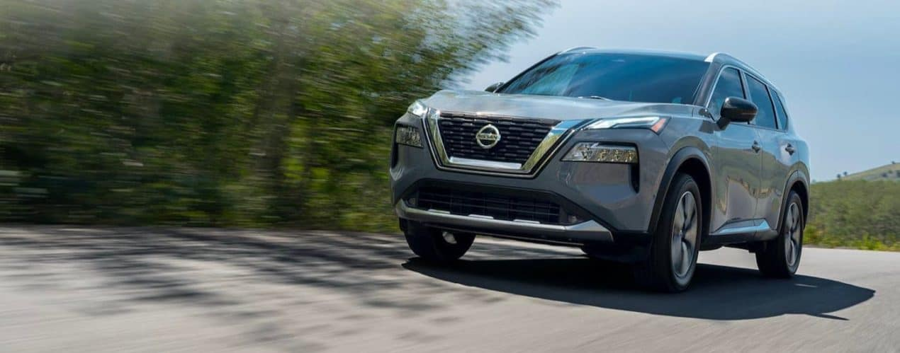 A grey 2021 Nisan Rogue is shown driving down a tree lined road after winning the 2021 Nissan Rogue vs 2021 Ford Escape comparison.