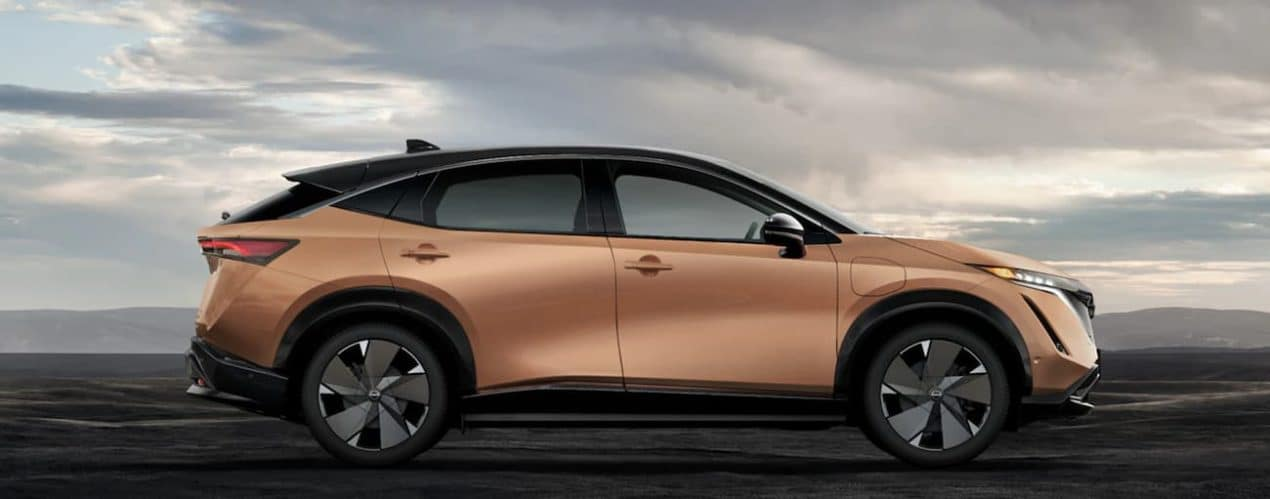 A gold 2022 Nissan Ariya is shown from the side parked in a desert.