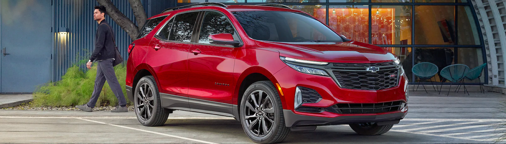 2022 Chevy Equinox RS in the color Cherry Red Tintcoat in front of a glass building.