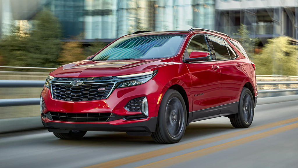 2022 Chevy Equinox RS in the color Cherry Red Tintcoat driving on city street.