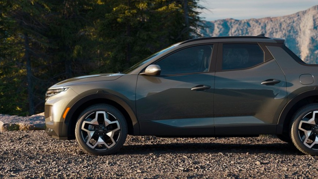 2022 Hyundai Santa Cruz in the color Sage Grey parked on a dirt road with trees in the background.
