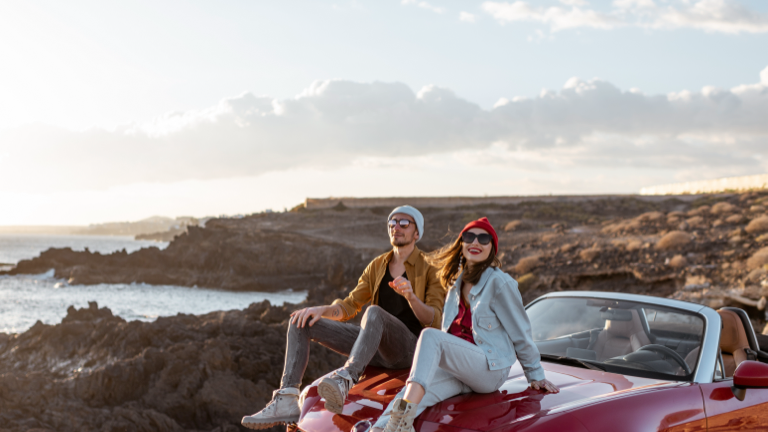 People on a read car facing the sea on a cliff edge.