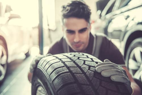 Mechanic inspecting tire