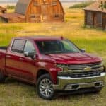 A popular Chevy truck for sale, a red 2020 Chevy Silverado 1500 LTZ, is parked in front of barns near Ennis, TX.