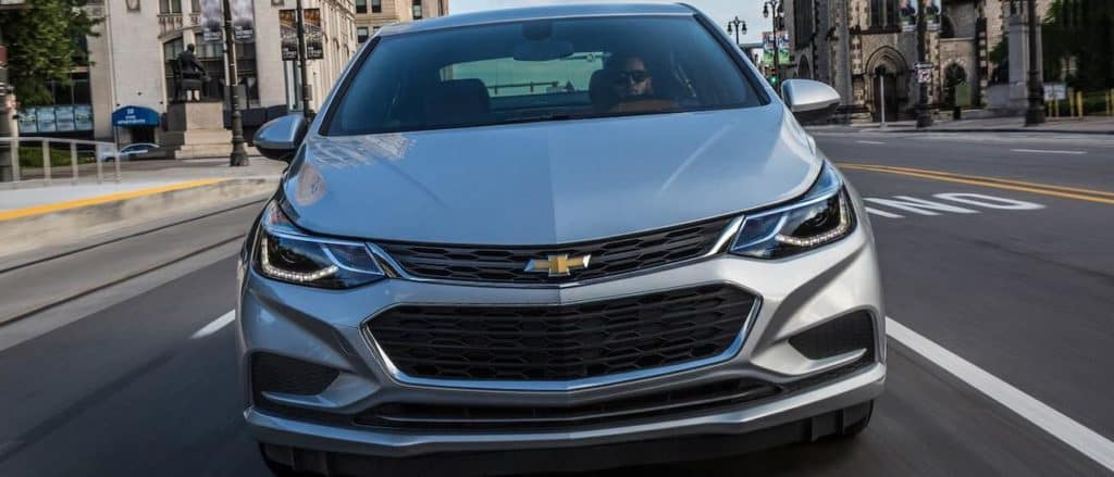 A silver 2017 Chevy Cruze is driving through a city. To find a Chevy Certified Pre-Owned car in Ennis, TX check out Frank Kent.