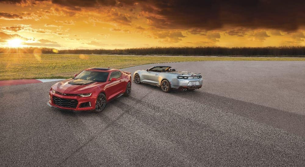 A red and a silver 2021 Chevy Camaro ZL1 coupe and convertible are parked on an empty lot at sunset.