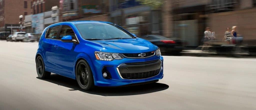 A blue 2019 Chevy Sonic, which can be found at a Chevy Dealership near Fort Worth, is driving down a city street.