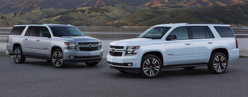 A grey 2020 Chevy Suburban is parked next to a white 2020 Chevy Tahoe, both great options for Chevy SUVs.