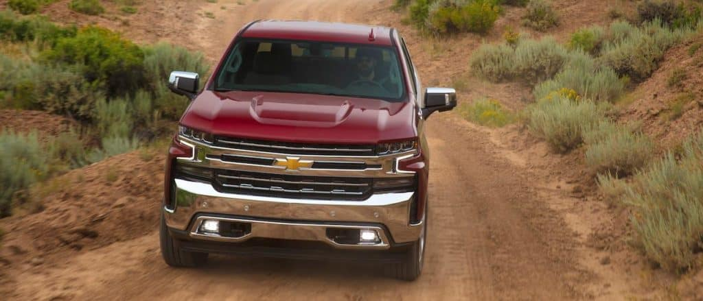 A red 2020 Chevy Silverado LTX is shown from the front, driving on a desert road outside Ennis, TX.