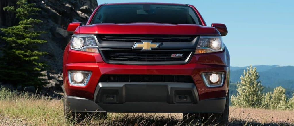 A red 2019 Chevy Colorado is shown from the front in the grass with mountains in the distance. Find other Chevy trucks for sale at our dealership.
