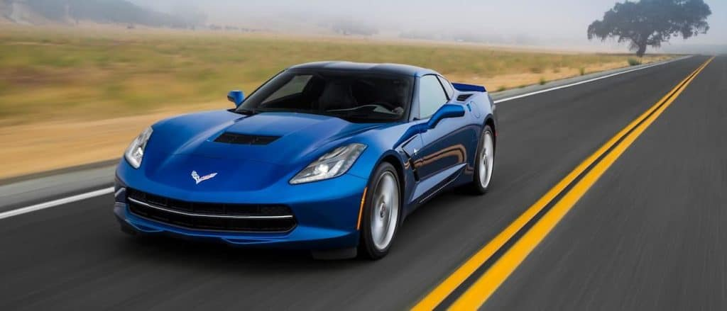 A blue 2016 Chevy Corvette is driving down a road near Ennis, TX with mist in the background.
