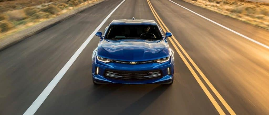 A blue 2016 Chevy Camaro, popular among used cars in Fort Worth, is driving on a sunny road.