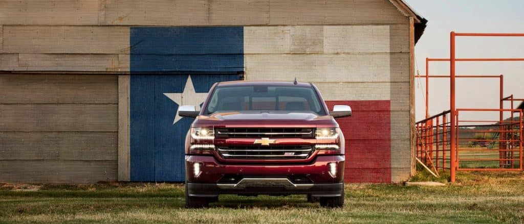 A red 2016 Chevy Silverado in front of a barn with the flag of Texas painted on it.