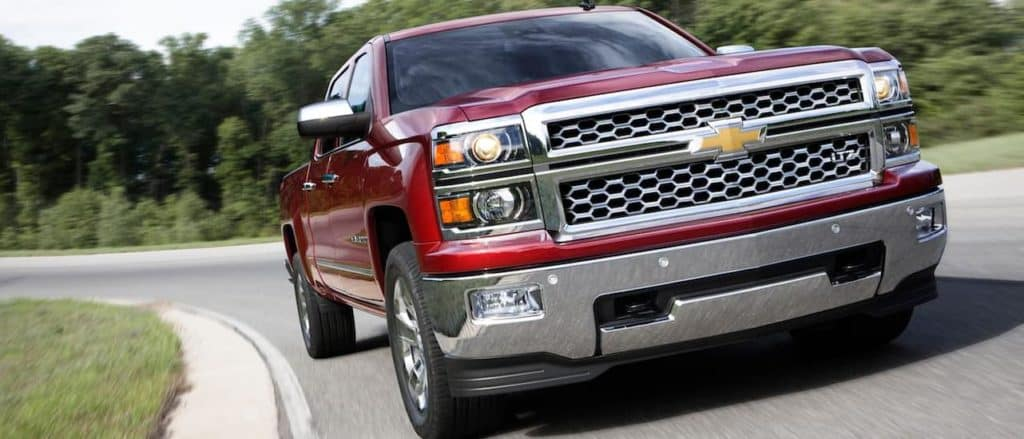 A red 2014 Chevy SIlverado LTZ from the front, driving.