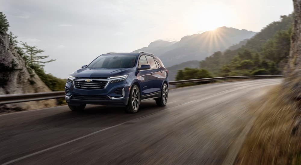 A blue 2022 Chevy Equinox is driving past mountains and a setting sun.